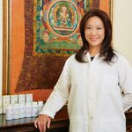 Asian lady standing next to a counter of Chinese herbal medicine with a Chinese green and orange mural in the background