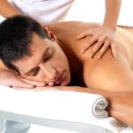 man with black hair lying on a white massage table with a woman's hands massaging his shoulders